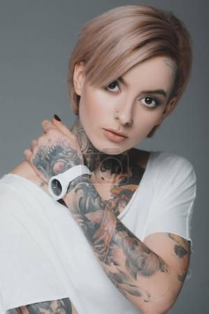 Photo for Portrait of beautiful tattooed girl in white t-shirt looking at camera isolated on grey - Royalty Free Image