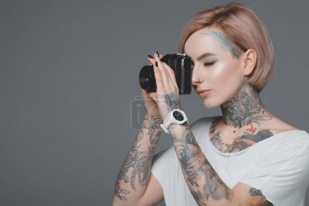 beautiful girl with tattoos photographing with camera isolated on grey