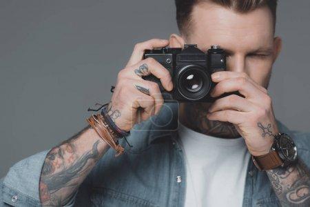 Photo pour Élégant jeune homme tatoué photographier avec caméra isolée sur fond gris - image libre de droit