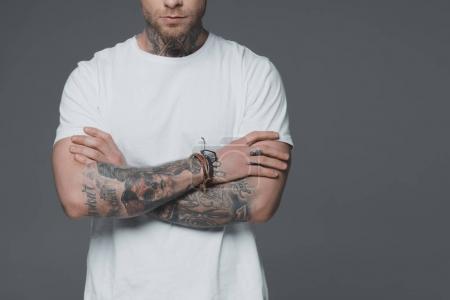 Photo pour Plan recadré de jeune homme tatoué debout avec les bras croisés isolés sur gris - image libre de droit
