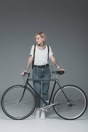 Photo for Beautiful stylish girl with tattoos standing with bicycle isolated on grey - Royalty Free Image