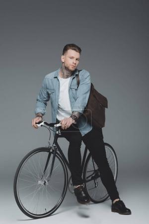 stylish young tattooed man sitting on bicycle and looking at camera on grey