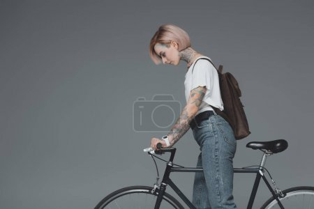 Photo for Side view of young woman with backpack standing with bicycle isolated on grey - Royalty Free Image