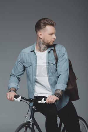 stylish young man with shoulder bag sitting on bicycle and looking away isolated on grey