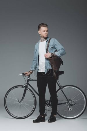 full length view of young tattooed man standing with bicycle and looking away on grey