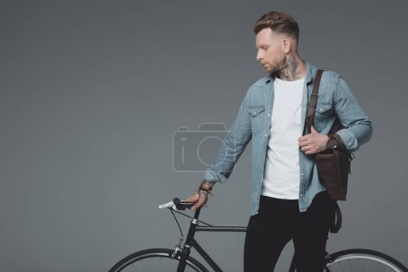 handsome young man with shoulder bag and bicycle standing isolated on grey