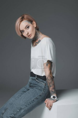 beautiful young woman with tattoos sitting and looking at camera isolated on grey