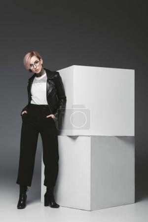 fashionable young woman in leather jacket and eyeglasses standing with hands in pockets and looking at camera in studio