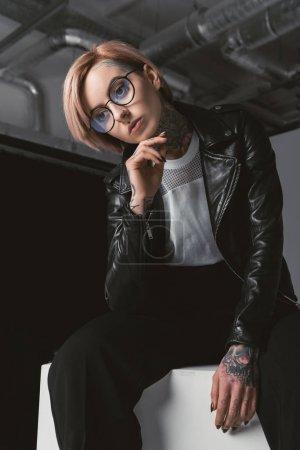 Photo pour Élégante jeune femme songeuse en lunettes et blouson de cuir, assis sur un cube blanc en studio - image libre de droit