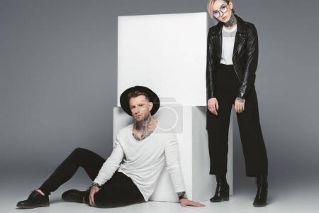 Photo pour La mode couple tatoué posant près de cubes blancs, isolés sur fond gris - image libre de droit
