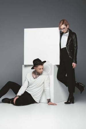 stylish tattooed couple posing near white cubes, isolated on grey