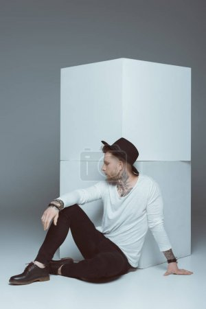 Photo for Stylish man in hat posing near white cubes, isolated on grey - Royalty Free Image
