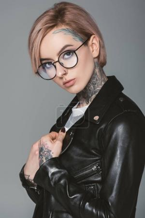 beautiful tattooed girl in eyeglasses and black leather jacket, isolated on grey