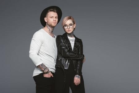 stylish tattooed couple posing together, isolated on grey