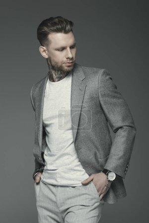 handsome tattooed businessman in grey suit, isolated on grey