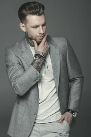 cher homme d'affaires tatoué en costume gris, isolé sur gris