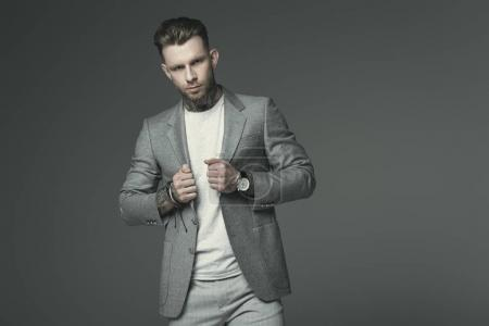stylish businessman in grey suit, isolated on grey