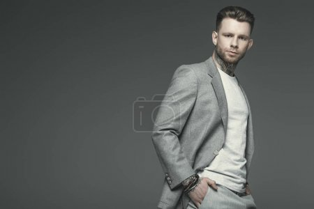 Photo for Handsome business man posing in grey suit, isolated on grey - Royalty Free Image