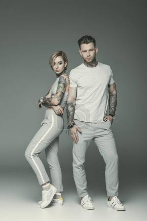 fashionable tattooed couple in sportswear posing together, isolated on grey