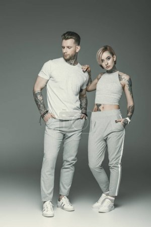fashionable tattooed couple in sportswear, isolated on grey