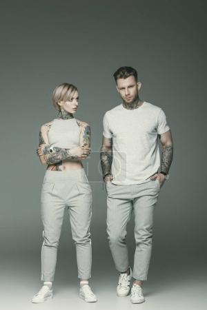beautiful tattooed couple in sportswear posing together, isolated on grey