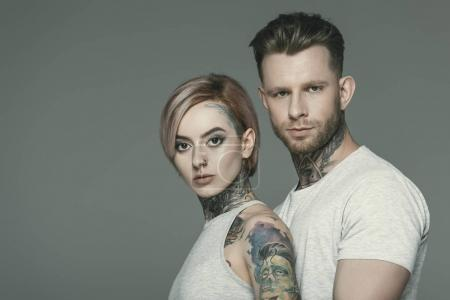 portrait of tattooed couple posing together, isolated on grey