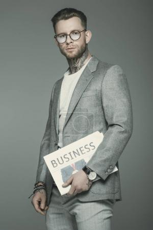 stylish businessman in eyeglasses and suit holding business newspaper, isolated on grey