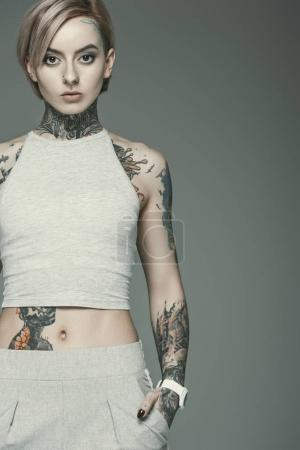 Photo for Beautiful tattooed girl, isolated on grey - Royalty Free Image