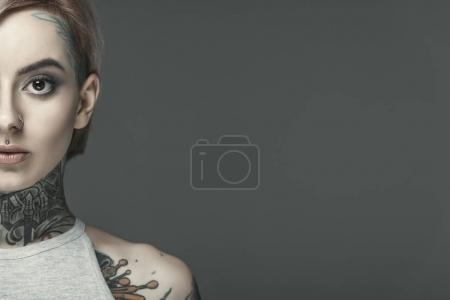 cropped view of beautiful tattooed girl, isolated on grey