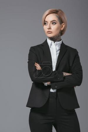 tattooed businesswoman posing in suit with crossed arms, isolated on grey