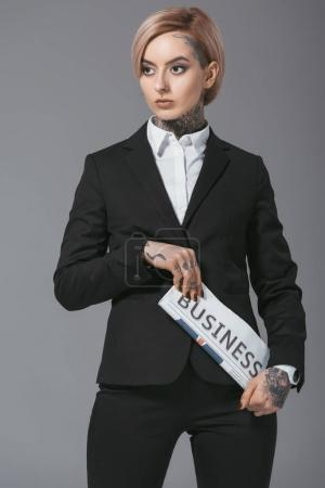 businesswoman with pink hair in suit holding business newspaper, isolated on grey