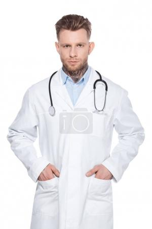 professional doctor with stethoscope and hands in pockets of white coat, isolated on white