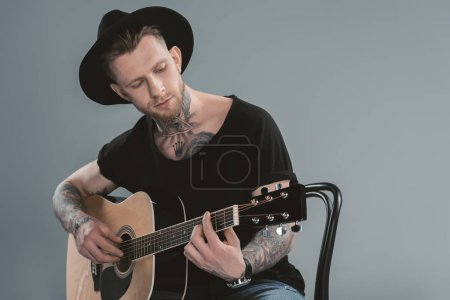 handsome tattooed guitarist in black hat playing on acoustic guitar, isolated on grey