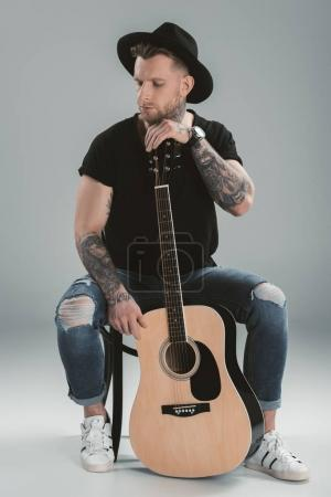 fashionable tattooed guitarist in black hat with acoustic guitar, isolated on grey