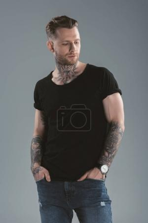 handsome tattooed man posing in casual clothes, isolated on grey