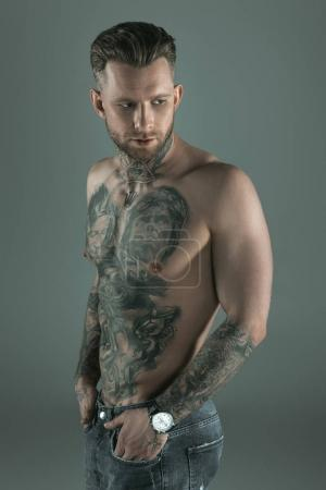 handsome shirtless tattooed man with hands in pockets, isolated on grey