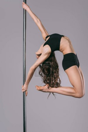young flexible pole dancer in sportswear training on grey