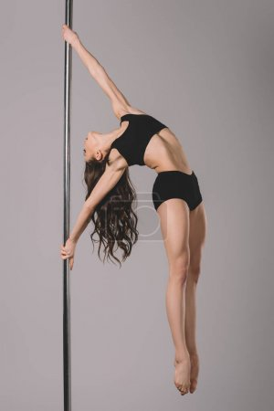 Photo for Full length view of attractive flexible girl dancing with pole on grey - Royalty Free Image