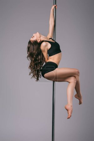 Photo for Side view of seductive young woman with closed eyes dancing with pole on grey - Royalty Free Image
