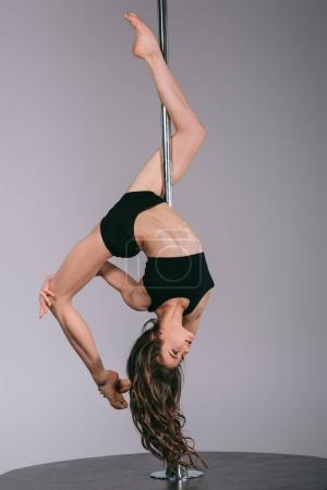 Photo for Beautiful flexible pole dancer exercising with pylon and looking away on grey - Royalty Free Image