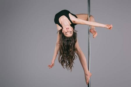 upside down of beautiful female dancer in sportswear exercising with pole and looking at camera on grey