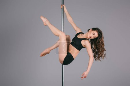 beautiful sporty girl dancing with pole on grey