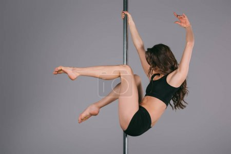 flexible athletic young woman dancing with pole on grey