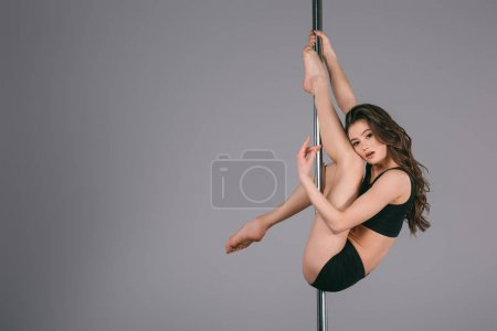 sensual young female dancer exercising with pole and looking at camera on grey
