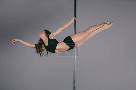 beautiful flexible athletic girl dancing with pole on grey
