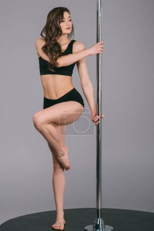 beautiful young female dancer exercising with pole and looking away on grey