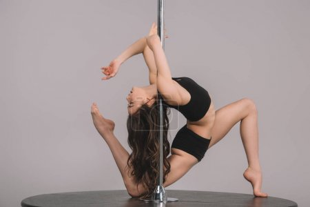 side view of beautiful flexible athletic girl exercising with pole on grey