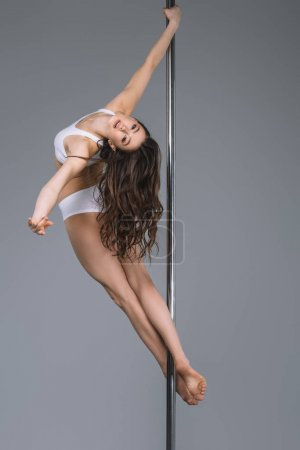 beautiful young woman looking at camera while dancing with pole on grey