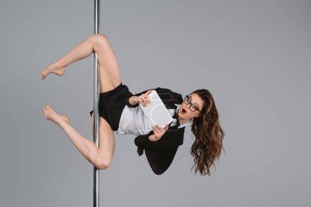 Photo pour Choqué jeune femme d'affaires dans les lunettes à l'aide d'une tablette numérique et l'exercice avec poteau sur gris - image libre de droit