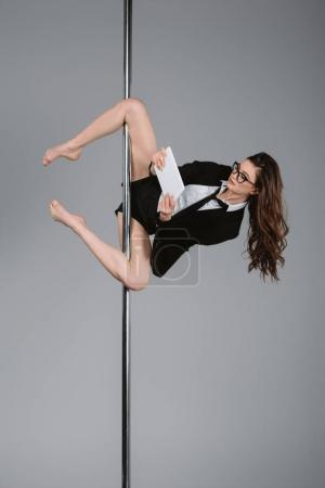 young businesswoman in eyeglasses using digital tablet and exercising with pole on grey